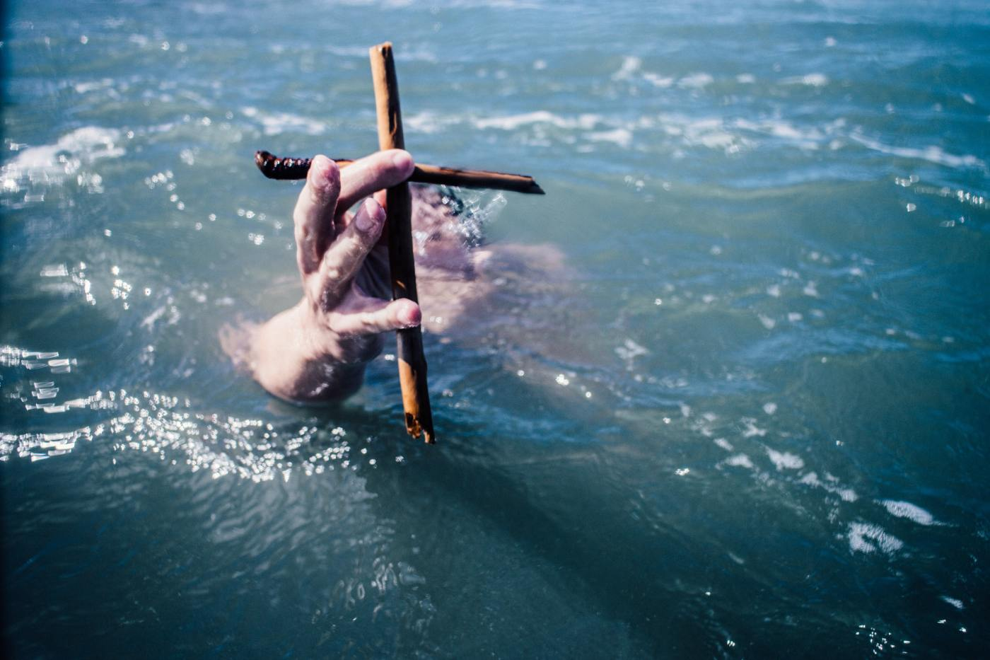 Ocean water with two clasping hands clutching a cross